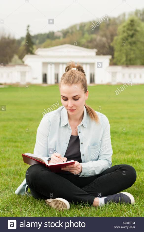 beautiful-woman-writing-in-her-diary-and-sitting-down-on-green-grass-G2BFHM